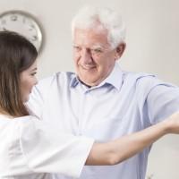 Senior man exercising with dumbbells during home rehabilitation